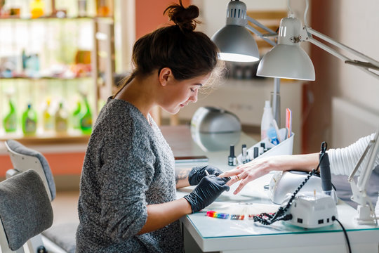 A young white manicurist girl makes a manicure to the client in the workplace. On her face a protective dressing, on her hands protective gloves.