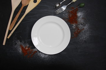 White plate with fork, spoon, salt, paprika on chalkboard. Ceramics, wood and steel. Food photo