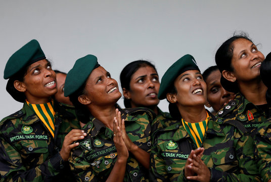 The female Special Task Force members looks up as they watching the sky divers at a demonstration during the 151st Sri Lanka's Police anniversary in Colombo