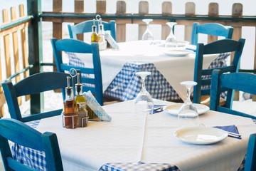Tables Set At Empty Outdoor Greek Restaurant