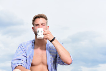 Sexy serious young macho holding cup of tea.