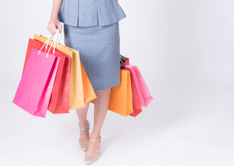 Closed up ,Hands of business women carrying colorful shopping bags isolated on white background.