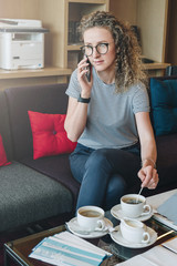 Young businesswoman is sitting on sofa in hotel lobby, cafe,drinking coffee and talking on her cell phone.
