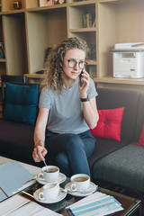 A young businesswoman in glasses is sitting on a sofa in the hotel lobby drinking coffee and talking on her cell phone.