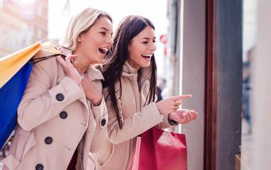 Shopping. Happy young women enjoying in shopping. Consumerism, fashion, lifestyle concept