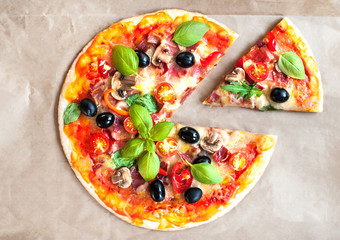 Pizza Margherita with cheese and basil leaf on baking craft paper background with fresh ingredients   for you to design and restaurant menu. Delicious Homemade Cheese  pizza.