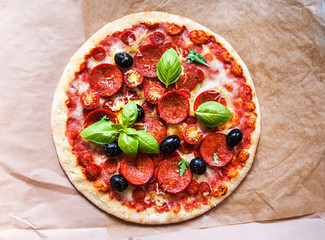 Pizza pepperoni with Ham, Pepperoni and Bacon on baking craft paper background with fresh ingredients   for you to design and restaurant menu. Delicious Homemade Meat  pizza.