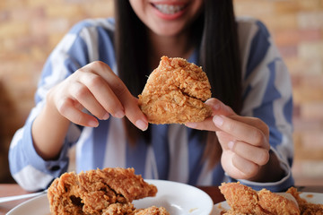 close up focus woman hand hold and showing fried chicken meal for eat at restaurant bar,fast food concept,healthcare living