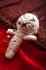 Witchcraft and place a jinx or put a spell on someone concept with a voodoo doll pierced by needles to cause harm to a victim leaning on a book of spells. Each needle represents a different curse