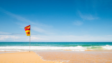 A word Swin Here on the red and yellow flags on the beach.To tell the point safe for swimming In security concept.