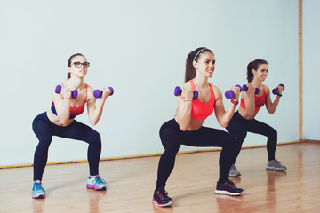 Three attractive sport girls doing squatting with dumbbells in fitness class.