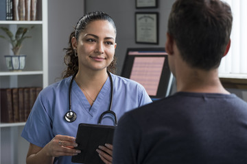 Hispanic female health professional advising male patient