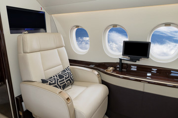 Comfortible cabin chair in the cabin of a modern business jet during flight.