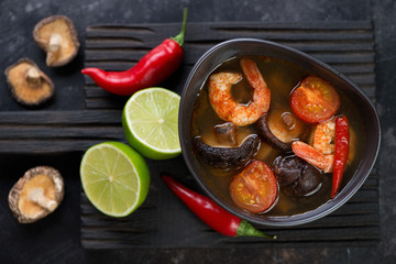 Thai hot Tom Yum soup on a black wooden serving board, flat-lay, horizontal shot