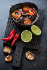 Bowl of thai Tom Yum soup on a black wooden serving board, selective focus