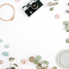Flat lay border frame with retro camera, eucalyptus branches, plate on white background. Top view artist background with space for text.