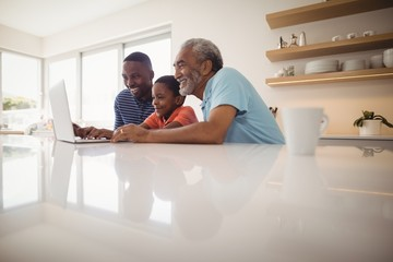 Multi-generation family using laptop in kitchen