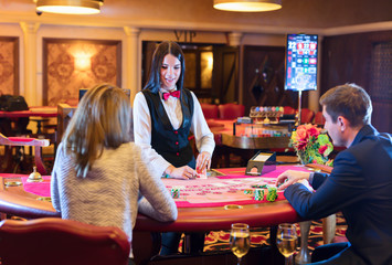 Cute lady casino dealer at poker table. Happy couple is playing Black Jack.