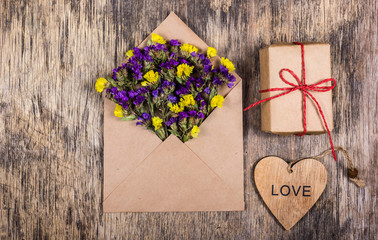 Dry field flowers in a paper envelope. Romantic letter. A wooden heart.