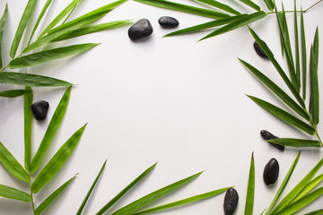 White paper with tropical leaf frame. Green bamboo leaf and sea beach pebbles flat lay.