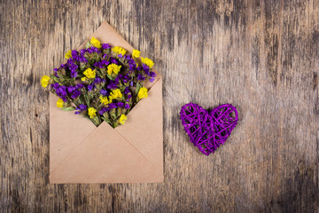 Wicker heart and wild flowers in an envelope. Romantic concept.