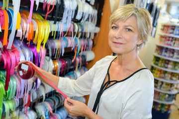 portrait of senior female owner of textile store