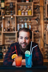 Handsome bearded barman is making blue lagoon and tequila sunrise cocktail in night club.