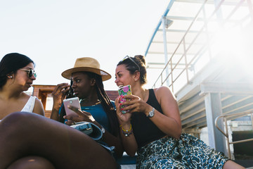 Friends with smart phones relaxing outside