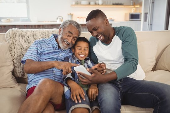 Smiling multi-generation family using mobile phone in living