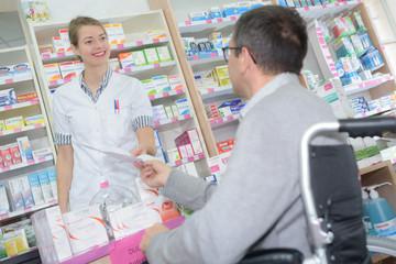 female pharmacist taking prescription from disabled man