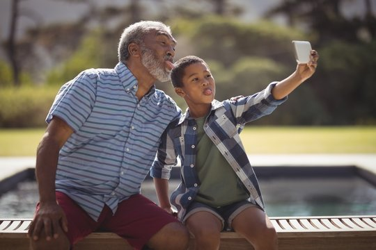 Grandson and grandfather taking selfie with mobile phone