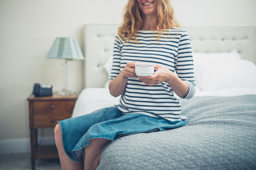 Happy woman in hotel room with cup