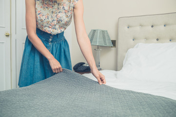 Young woman making the bed