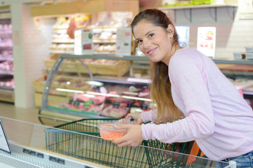 woman pushing a shopping trolley in supermarket