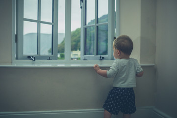 Little baby standing by window of country house