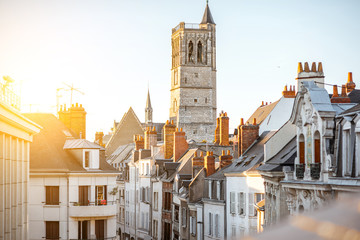 Top cityscape view on the old buildings and curch tower in Orleans city during the sunset in central France