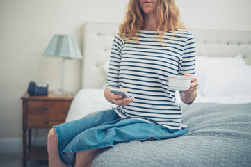 Woman with cup and smart phone in hotel room