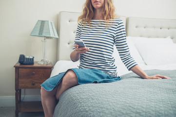 Woman on bed in hotel room using smart phone