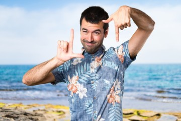 Handsome man with flower shirt focusing with his fingers at the beach