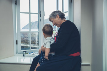 Senior woman with grandchild by the window