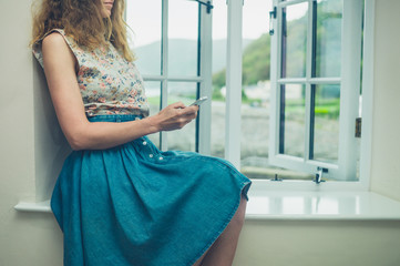 Woman using her phone by window of country house