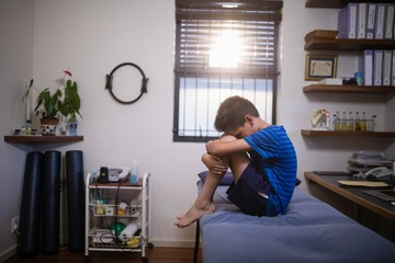 Side view of boy sitting on bed in pain