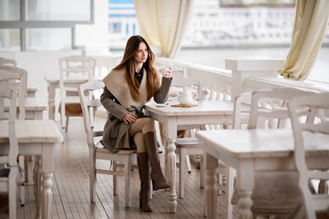 Woman in autumn coat posing in old cafe. Autumn day