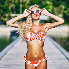 Blonde woman in bikini and sunglasses outdoor portrait