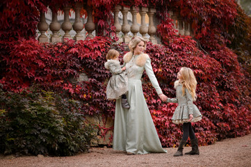 Mom and daughters outdoors. Autumn day.