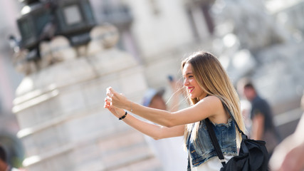 Pretty tourist teenager taking a photo with her mobile phone. Photo taken in Milan, Italy