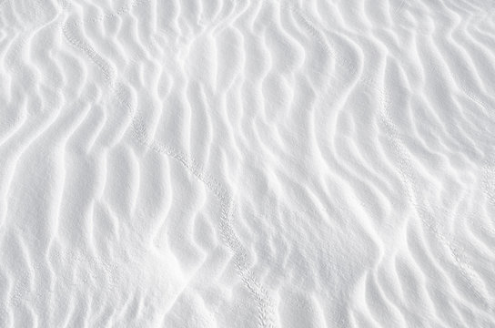 White sand texture background with wave pattern and insect trails