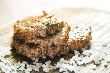 beef steak with herbs and salt on cutting board in sunlight