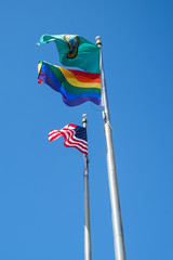American, State of Washington, and Gay Pride flags in breeze