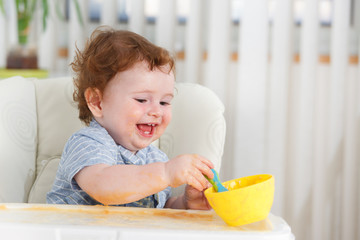 Cute baby boy eating by himself on high chair
